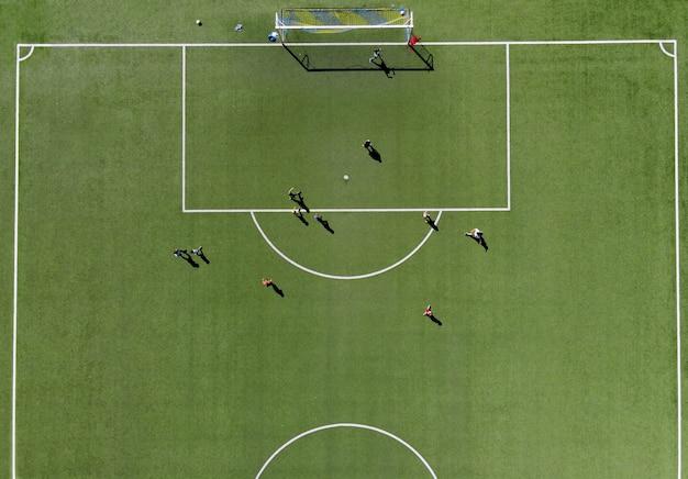 Piłkarze grający mecz na zielonym boisku, oglądany bezpośrednio z góry z drona w słoneczny letni dzień