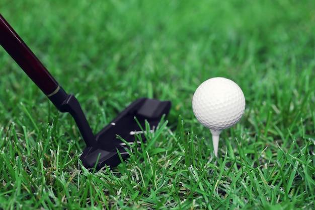 Piłki golfowe i kierowca na zielonej trawie
