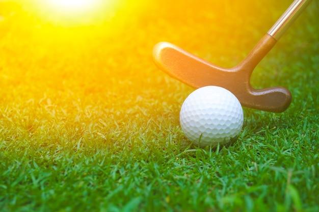 Piłki golfowe i kije są umieszczane na trawniku. kij golfowy uderzając białą piłeczkę golfową z zieloną trawą.