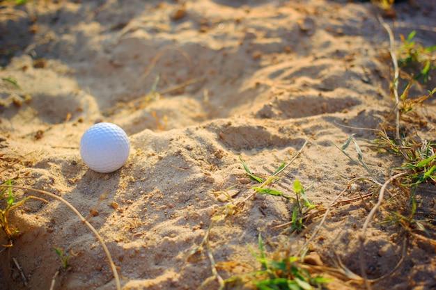 Piłki golfowe na piasku na polu golfowym.