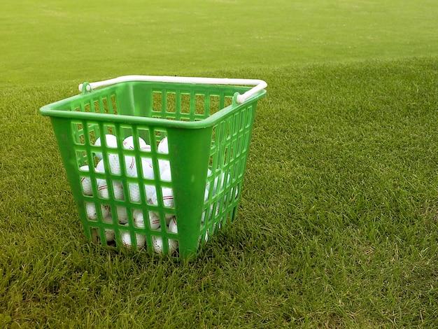 Piłki golfowe w koszu na trawy tle.