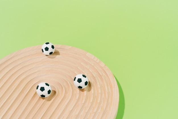 Piłki nożnej na drewnie na zielonym tle. koncepcja piłki nożnej i sportu.