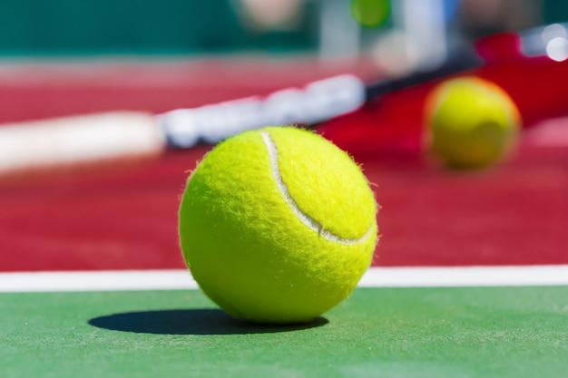 Piłki tenisowe i rakieta na trawiastym boisku