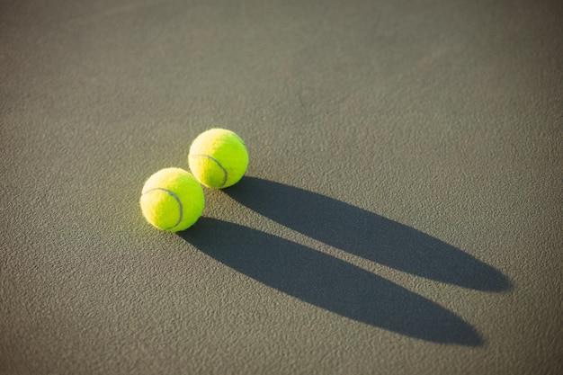 Piłki tenisowe trzymane na korcie