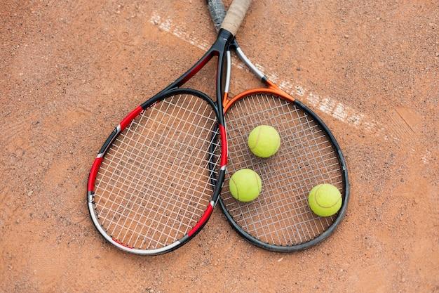 Piłki tenisowe z rakietami na korcie