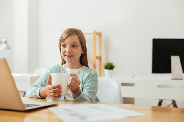 Pilna genialna piękna dziewczyna siedzi przy stole i czyta coś na swoim komputerze