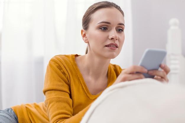 Pilna odpowiedź. przyjemna, przemyślana, atrakcyjna kobieta przy użyciu telefonu, patrząc na ekran i pozując na świetle