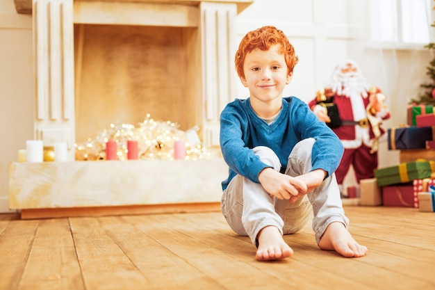 Pilne dziecko. niski kąt strzału rudego chłopca relaksującego na drewnianej podłodze z radosnym uśmiechem na twarzy w domu.
