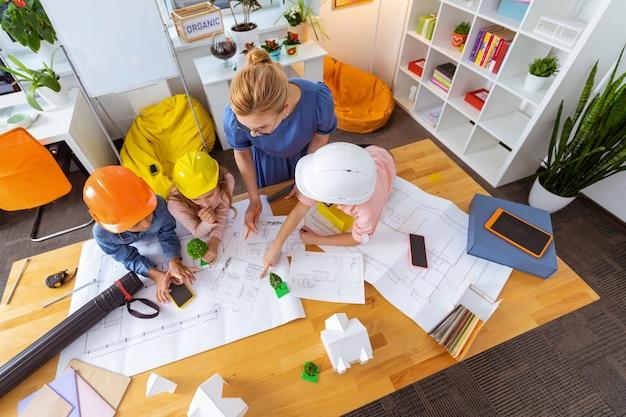 Pilni uczniowie. widok z góry na blond nauczycielkę i pilnych uczniów modelujących inteligentne miasto i rysujących szkice