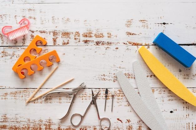 Pilniki, nożyczki, szczypce, cekiny i lakiery do paznokci na białym tle drewnianych.