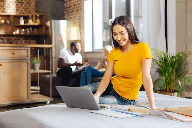 Pilny uczeń. atrakcyjna brunetka młoda kobieta siedzi na łóżku, patrząc na ekran i uśmiechając się