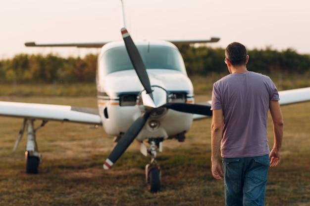 Pilot człowiek idący obok małego prywatnego samolotu.