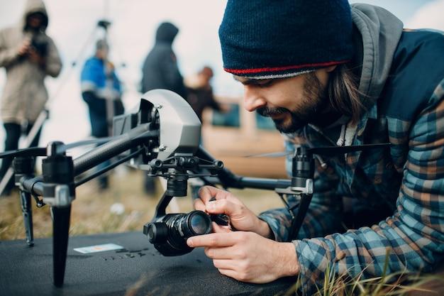Pilot-człowiek sprawdzający kamerę drona quadkoptera przed lotem lotniczym i filmowaniem