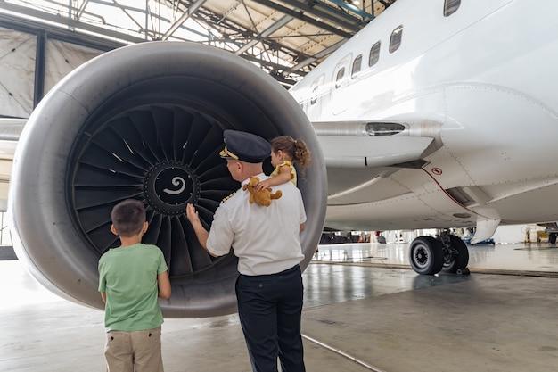 Pilot i dzieci stoją przy turbinie i patrzą na nią