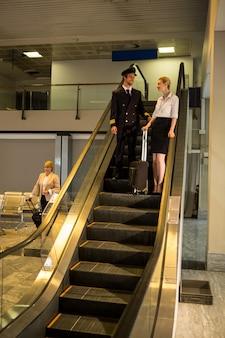 Pilot i personel rozmawiają na schodach ruchomych
