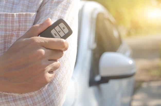 Pilot samochodowy za pomocą inteligentnego klucza, ręka trzymająca inteligentny klucz do blokowania drzwi białego samochodu;