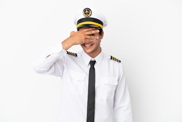 Pilot samolotu na odosobnionym białym tle zakrywającym oczy rękami i uśmiechniętym