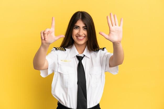 Pilot samolotu na żółtym tle, licząc siedem palcami