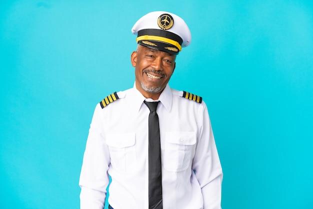 Pilot samolotu starszy mężczyzna na białym tle na niebieskim tle, śmiejąc się w pozycji bocznej