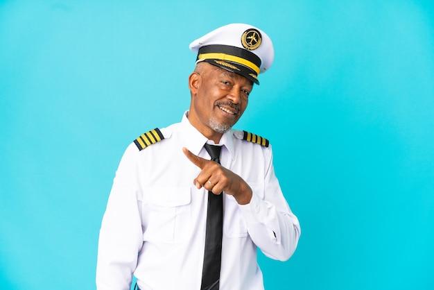 Pilot samolotu starszy mężczyzna na białym tle na niebieskim tle wskazujący na bok, aby zaprezentować produkt
