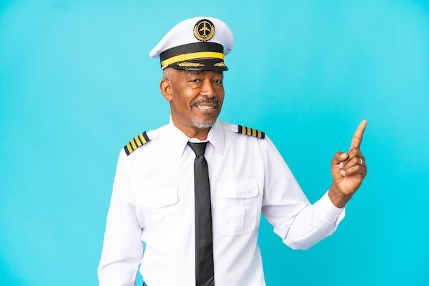 Pilot samolotu starszy mężczyzna na białym tle na niebieskim tle wskazujący świetny pomysł