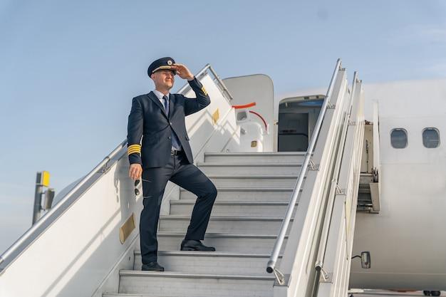 Pilot w czarnym garniturze stojący na schodach samolotu