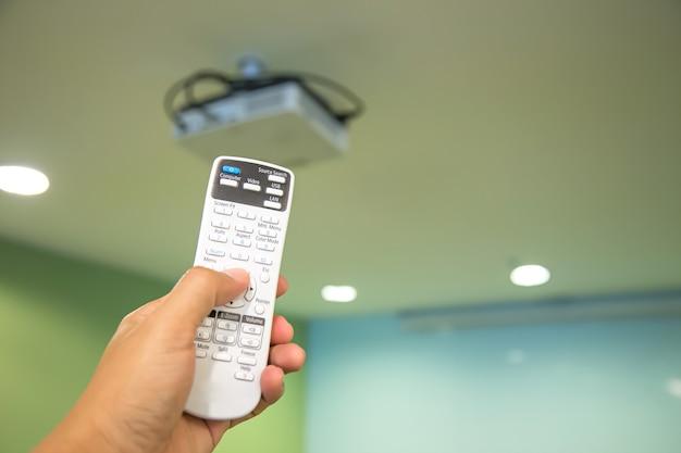 Pilot zdalnego sterowania włącz sufitowy projektor cyfrowy w sali konferencyjnej.