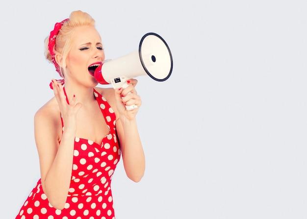 Pin up girl w czerwonej sukience krzyczy przez megafon