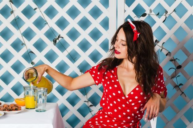 Pin-up girl w czerwonej sukience siada przy stole i nalewa sok.