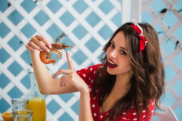 Pin-up girl w czerwonej sukience siada przy stole i wskazuje palcem na krewetki. zbliżenie