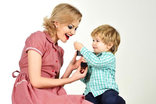 Pin up kobieta z małym chłopcem matka przedstawia mały prezent dla syna dzień matki pin up kobieta w czerwieni