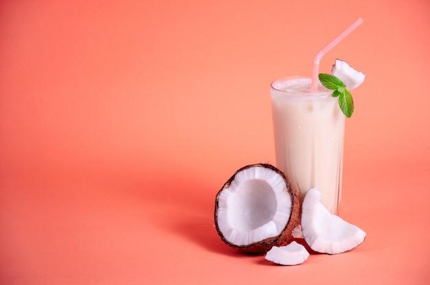 Pina colada - tropikalny koktajl z sokiem ananasowym, mlekiem kokosowym i rumem. świeży letni napój z krakingowym kokosem i mennicą na koralowym tle. skopiuj miejsce na tekst