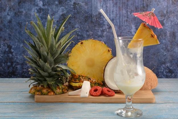 Piña colada ze świeżymi owocami na drewnianej desce do krojenia na białym stole i niebieskim tle