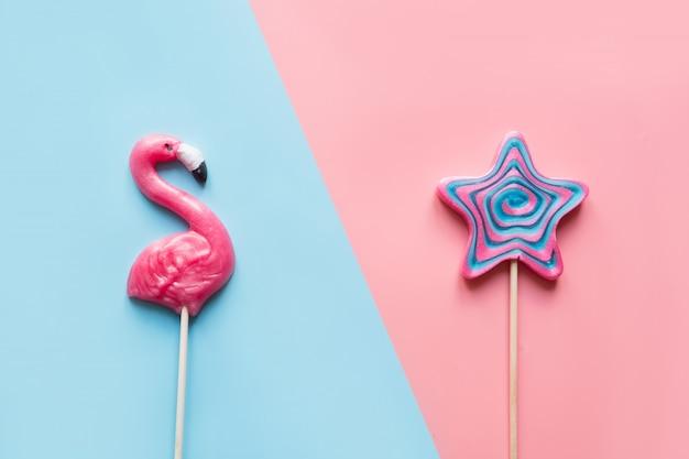 Pink flamingo i lollipop candy star na niebiesko-różowo.