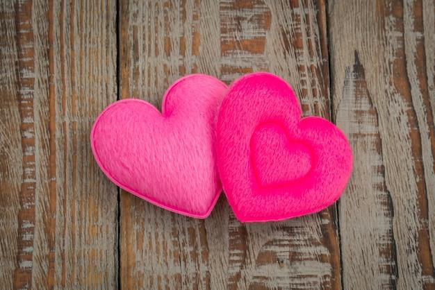 Pink heart poduszki na tle drewna.