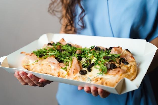 Pinsa romana w białym pudełku tekturowym. kobieta gospodarstwa crocchiarella wyśmienita kuchnia włoska na białym tle. pinsa z mięsem, rukolą, oliwkami, serem.