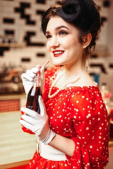 Pinup girl picie napoju gazowanego w kawiarni retro