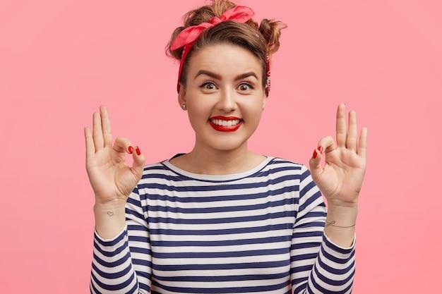 Pinup retro kobieta z makijażem, zdrową skórą, nosi sweter w paski i opaskę, ma szeroki uśmiech, robi dobry gest, pokazuje, że wszystko jest w porządku