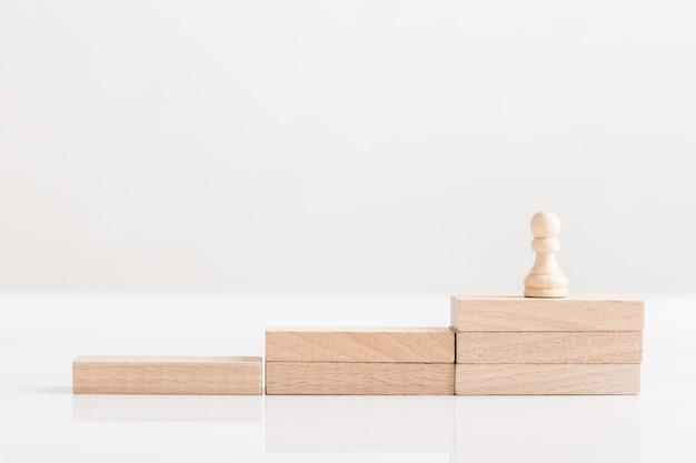 Pionek szachowy na schodach z drewnianych cegieł, koncepcyjne wizji biznesowej.
