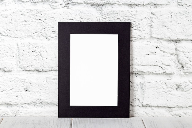 Pionowa czarna ramka na drewnianym stole. makieta z miejsca na kopię