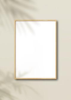 Pionowa drewniana ramka na zdjęcia wisząca na jasnobeżowej ścianie.