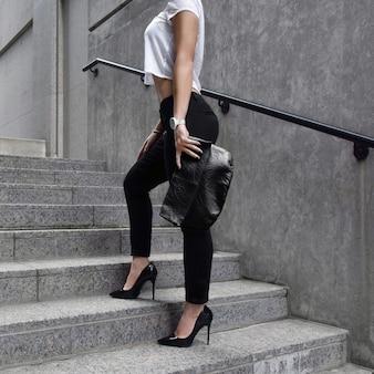 Pionowa elegancka kobieta pozuje na schodach trzymając torebkę
