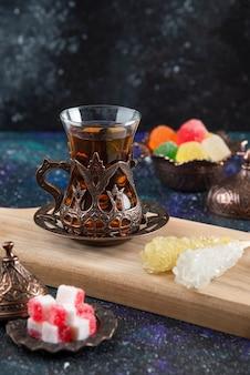 Pionowa gorąca herbata i słodkie cukierki na drewnianym baord