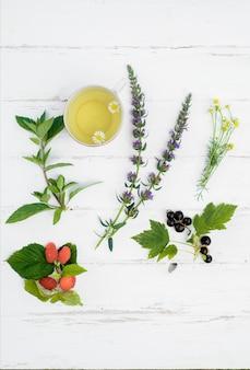 Pionowa gorąca herbata na drewnianym białym tle, składniki do przygotowania naturalnej herbaty ziołowej