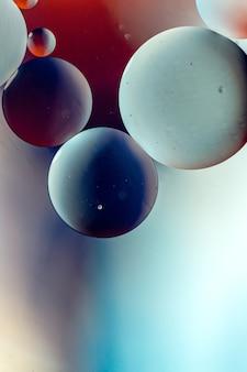 Pionowa graficzna ilustracja okręgów w ciemnych kolorach na jasnoniebieskim i czerwonym tle