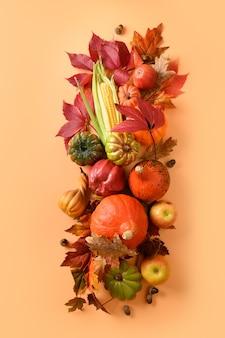 Pionowa kompozycja jesiennych zbiorów, dynie, kolby kukurydzy, kolorowe jesienne liście na pomarańczowym tle. widok z góry. święto dziękczynienia i halloween.