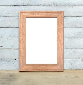 Pionowa makieta starej drewnianej ramy a4 stoi na drewnianym stole na pomalowanym białym tle drewnianych. styl rustykalny, proste piękno. renderowania 3d.