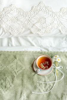 Pionowa, oliwkowa krata, filiżanka naturalnej herbaty ziołowej z mięty i melisy w łóżku, poranne zbliżenie. przytulna atmosfera. ażurowa koronka, bawełniany biały koc, letnie stokrotki, prowansja i styl retro.