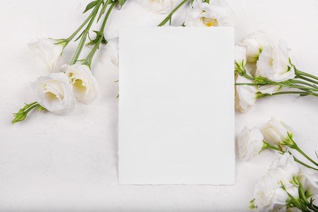 Pionowa pusta makieta karty 7 x 5 z kwitnącymi białymi kwiatami eustoma lisianthus, element projektu na zaproszenie na ślub, dziękuję lub kartkę z życzeniami. wiosna w tle