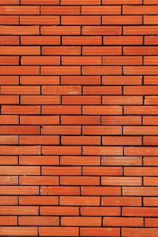 Pionowa ściana z czerwonej cegły.